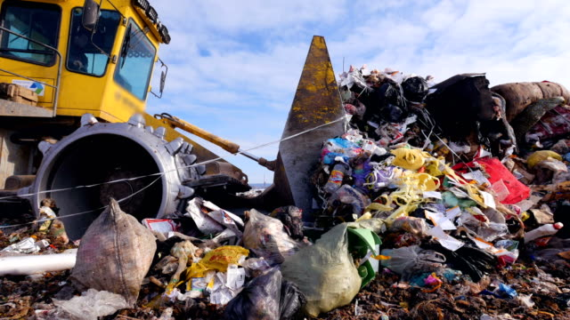 Enviromet pollution concept. A low angle view on a landfill compactor moving trash. video