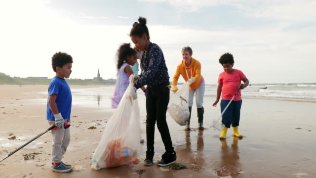 Environmental Beach Cleanup A group of volunteers teaming up at the beach. Plastic bags in hand and plastic grabbers at the ready. All wearing protective gloves, wellies and taking care of the environment. cleaning stock videos & royalty-free footage