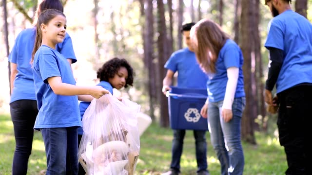 Environmental clean up. Volunteers pick up trash in local park. Multi-ethnic group of environmental volunteers pick up trash at local park during spring season.  They use garbage bags and recycling tubs.  Group exits park at end of video.  Few seconds at end of empty park. sociology stock videos & royalty-free footage