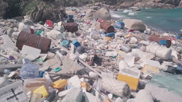 Environmental destruction caused by beach covered in plastic and rubbish causing climate change in Hong Kong. Aerial drone view