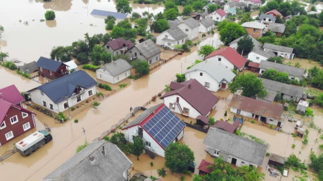 environmental disaster and climate change. aerial view river that flooded the city and houses. flooded houses in the water. - uragano video stock e b–roll