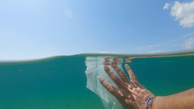 umweltprobleme: reinigung des ozeans, handentfernen von plastiktüten. - plastikmaterial stock-videos und b-roll-filmmaterial