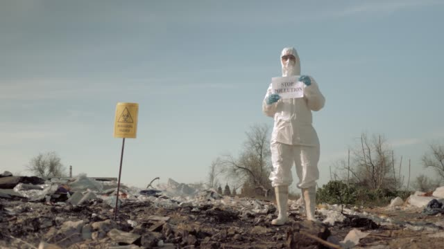 environmental movement, girl in mask and costume holding poster with stop pollution slogan at trash dump with sign biological hazard