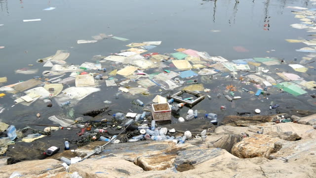 環境汚染です。プラスチック ボトル、バッグ、川や湖でゴミ。ゴミや汚染水に浮かんでいます。汚染された海岸に沿ったモーション。クローズ アップ - 水に浮かぶ点の映像素材/bロール