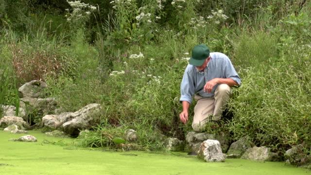 Científico medioambientales tomar una muestra de agua - vídeo