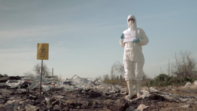 environmentalism, woman in protective costume and mask holding poster with stop pollution slogan at landfill site with garbage near sign biological hazard