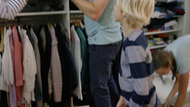 vídeos de stock e filmes b-roll de environmentally aware family packing clothes for reuse - economia circular
