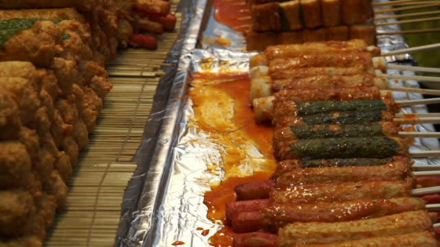 Eomuk, Korean street food. Fried fish cake on stick with red sauce in Seoul, Korea video