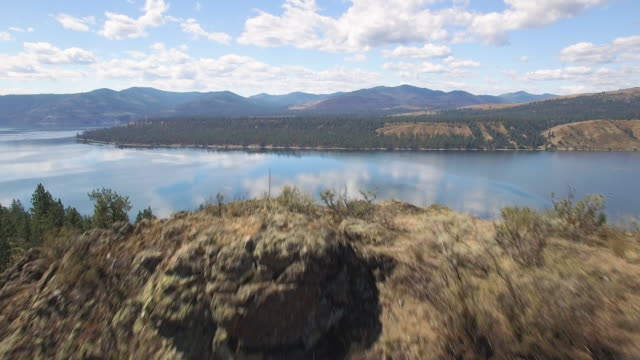 Epic Aerial Over Rocky Cliff to Reveal Lake Roosevelt Washington on Sunny Day Drone flying over desert cliff edge to scenic view of big forest lake on sunny day national landmark stock videos & royalty-free footage