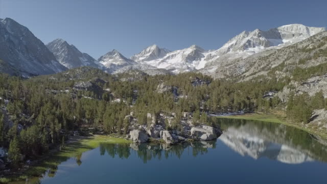 epic aerial reveal snow mountain valley with lake mirror reflection - inyo national forest, little lakes valley trail (gem lakes), bishop, ca - park narodowy yosemite filmów i materiałów b-roll