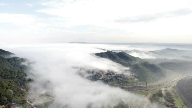 Épica vista aérea de uma cidade do Brasil, ao redor da montanha coberta com um nevoeiro duro no meio do dia - vídeo