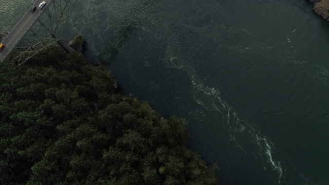 Epic Aerial with Slow Pan from Forest Trees to Big Bridge Crossing Ocean Islands in Pacific Northwest video