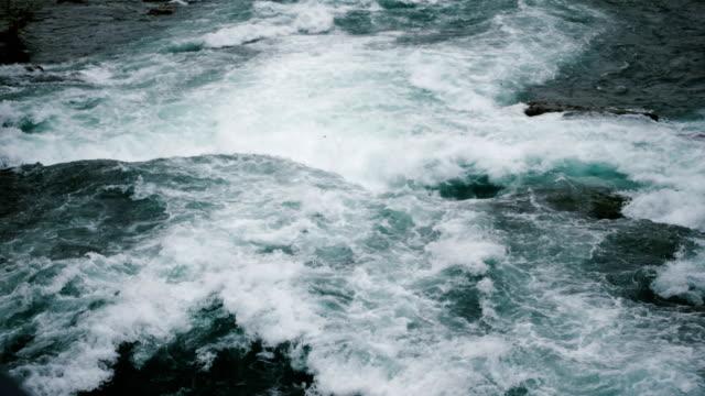 Epic close-up top view shot of powerful natural streams of water and foam rushing down at Niagara River slow motion.