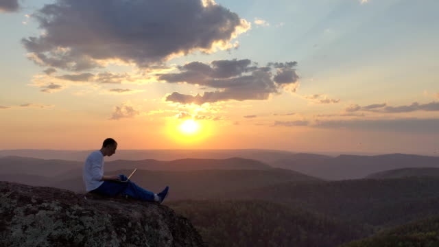 Epic drone shot of a silhouette of a young freelancer with a laptop on the edge of a rock ledge in the mountains. Epic drone shot of a silhouette of a young freelancer with a laptop on the edge of a rock ledge in the mountains. 4K minority groups stock videos & royalty-free footage
