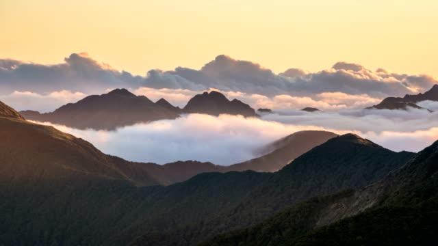 storslagen kväll med moln i dimmiga fjäll natur i nya zeelands vilda landskap vid solnedgången tids fördröjning - offline bildbanksvideor och videomaterial från bakom kulisserna