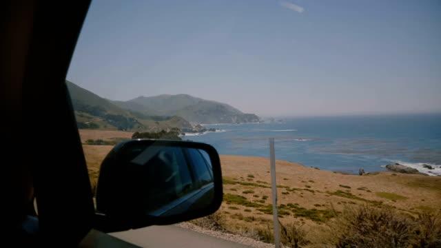 vídeos de stock e filmes b-roll de epic in-car shot of amazing sunny big sur ocean beach coast and rocks, concept of road trip along iconic highway 1. - big sur