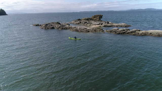 Epic Kayaking Aerial Passing Man Paddling by Islands in Pacific Ocean video