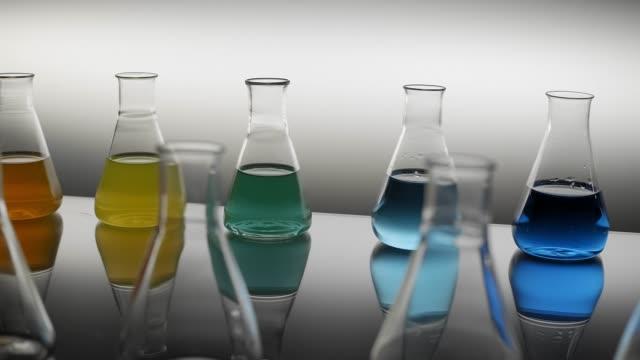 테이블에 반사하는 액체로 채워진 에를렌마이어 플라스크 - formula 1 스톡 비디오 및 b-롤 화면