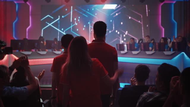 esport team of professional gamers wchodzi na arenę mistrzostw gier wideo. cyber games tournament event z tłumem fanów dopingujących ulubionych graczy. transmisja strumieniowa online. zwolnionym - współzawodnictwo wydarzenia filmów i materiałów b-roll