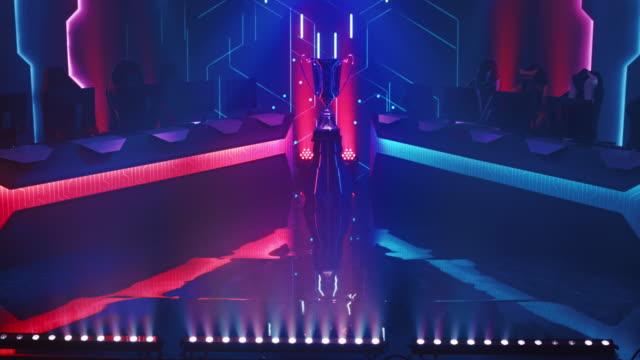 trofeum zdobywcy e-sportu na scenie w środku komputerowej hali mistrzostw w grach wideo. dwa rzędy pc dla konkurencyjnych drużyn. stylowe neony z chłodnym designem. dolly strzał - współzawodnictwo wydarzenia filmów i materiałów b-roll
