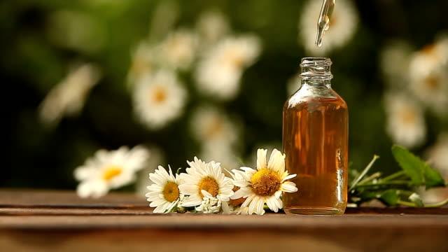 vídeos y material grabado en eventos de stock de esencia de flores en la mesa en la hermosa botella de vidrio - manzanilla