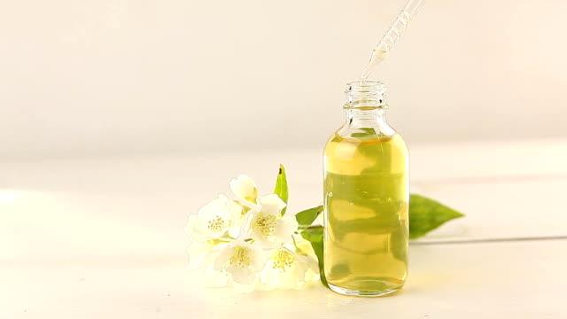 vídeos de stock e filmes b-roll de essence of flowers on white background in beautiful glass jar - fitoterapia