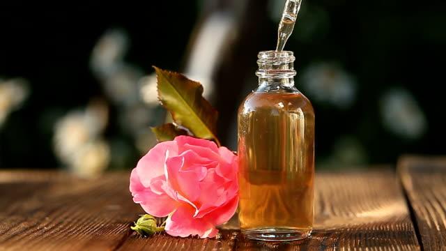 美しいガラスの瓶の中のテーブルの上のバラのエッセンス - 芳香点の映像素材/bロール