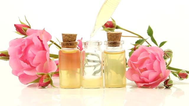 vídeos de stock e filmes b-roll de essence of rose on white background in beautiful glass bottle - aromaterapia