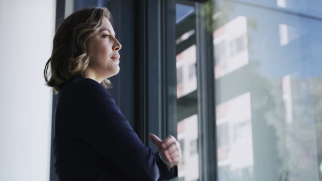 Establishing a vision for the future of her business 4k video footage of a young businesswoman looking thoughtfully out the window in an office looking at view stock videos & royalty-free footage
