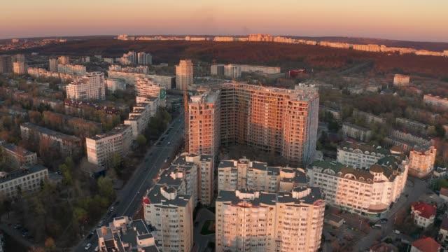 establishing aerial shot of chisinau, moldova at sunset - молдавия стоковые видео и кадры b-roll