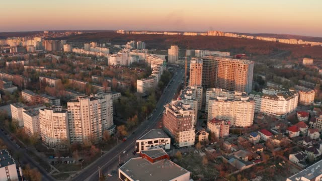establishing alow push aerial shot of chisinau, moldova at sunset - молдавия стоковые видео и кадры b-roll