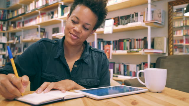 Establishing new ideas. Beautiful black woman spending her afternoon in a quiet library. She gets to clear her mind and think of new ideas for the upcoming projects. textbook stock videos & royalty-free footage