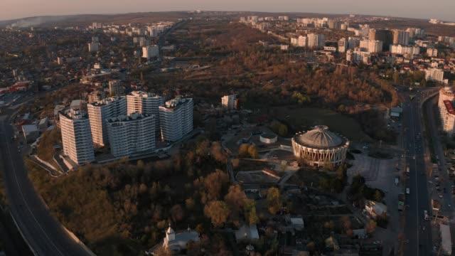 establishing orbiting aerial shot of chisinau, moldova at sunset - молдавия стоковые видео и кадры b-roll