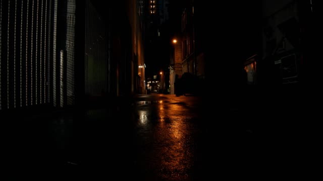 Establishing shot of a dark alleyway at night. Establishing shot of a dark alleyway at night. Atmospheric 4K footage. Shot on a cinema camera in RAW. No discernible faces or logos. alley stock videos & royalty-free footage