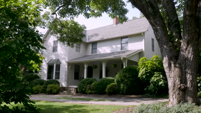 Establishing shot of a large two story house surrounded by large old trees Establishing shot of a large two story grey house with a covered front porch surrounded by large old trees - dolly shot mansion stock videos & royalty-free footage