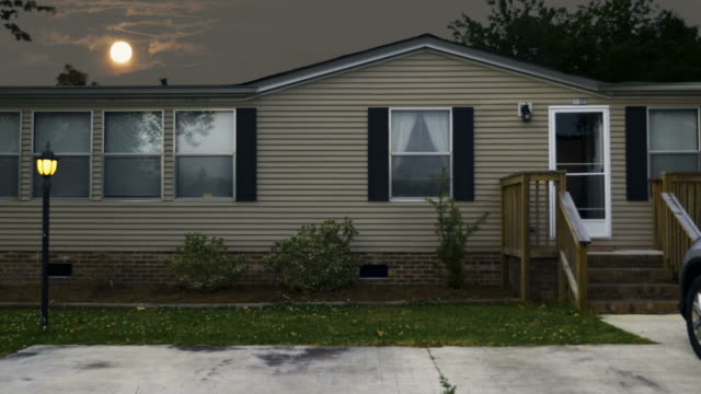 Establishing shot of a manufactured home with a full moon rising over it's roof