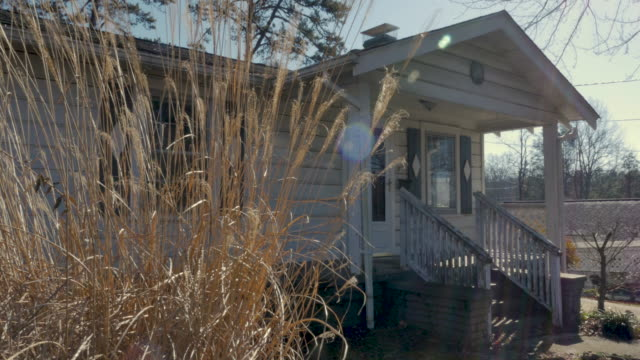 Establishing shot of a small one story house with tall dead grass