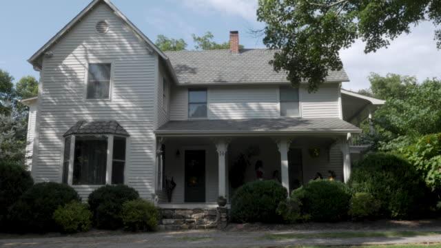 vidéos et rushes de tournage d'une maison grise de deux étages avec la voie d'évitement en bois en été - emballé