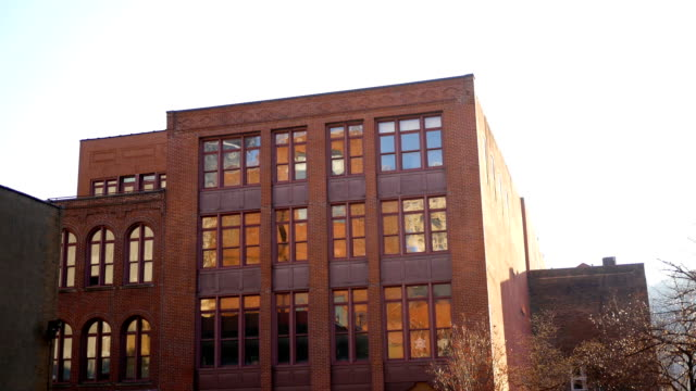 Establecer toma de edificio de ladrillo en ciudad urbana cerca de puesta del sol - vídeo