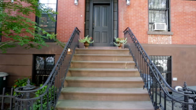 Establishing shot of brownstone building from stairs video
