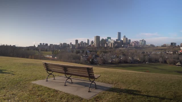 Establishing shot of Edmonton skyline with a bench in the foreground