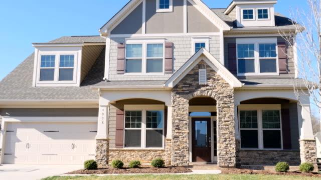 vídeos de stock e filmes b-roll de establishing shot of large new house with a 2 car garage in a suburb development - driveway, no people