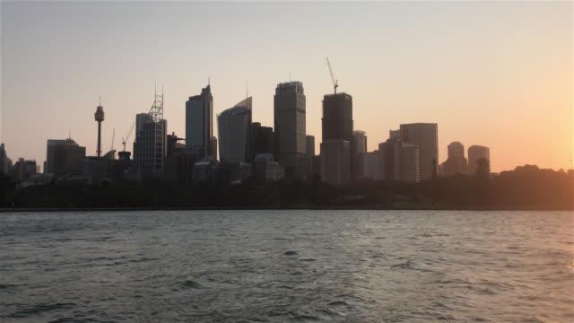 Establishing shot of Sydney city skyline at harbour during sunset. video
