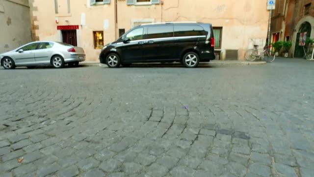Establishment shot of Rome traditional building on pavement street