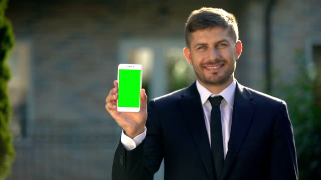 Estate agent holding smartphone with green screen, app for housing rental Estate agent holding smartphone with green screen, app for housing rental salesman stock videos & royalty-free footage