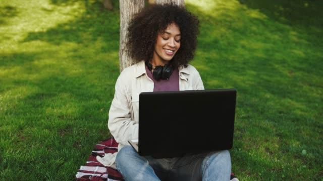 etnisk svart dam i vardagskläder. hon ler, talar med hjälp av online video samtal på laptop, sitter på rutig matta i parken. slow motion, närbild - naturparksområde bildbanksvideor och videomaterial från bakom kulisserna