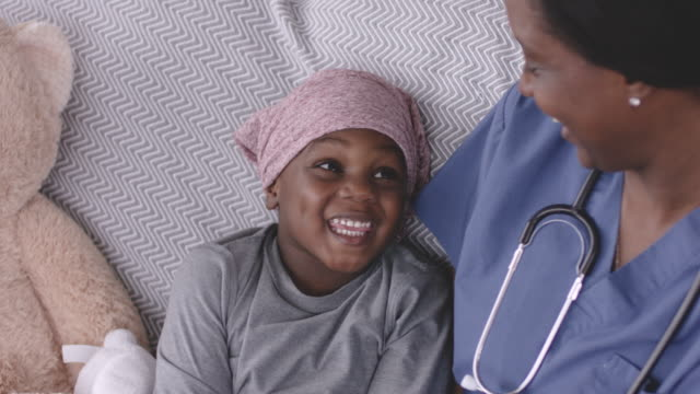 Ethnic Boy With Cancer Smiling At His Nurse A black child with cancer is wearing a scarf on his head. He is sitting on a couch with his nurse. The two are smiling at one another. There is a large teddy bear sitting next to the child. cancer patient stock videos & royalty-free footage