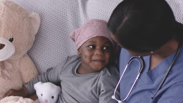 vídeos de stock e filmes b-roll de ethnic boy with cancer smiling at his nurse - melhoria