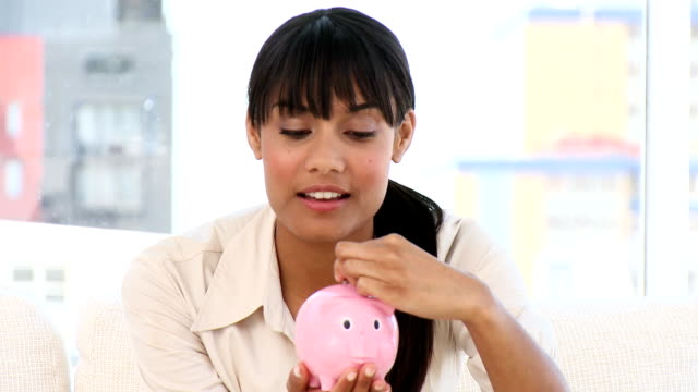 Ethnic businesswoman holding a piggy-bank video