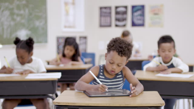Ethnic Elementary Student Working On A Digital Tablet In A Classroom A young elementary school student is focused during class while sitting at his desk and working on a digital tablet and stylus. primary school stock videos & royalty-free footage